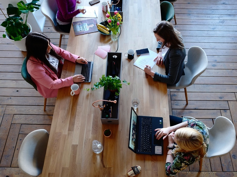 three ladies working on laptops at a table