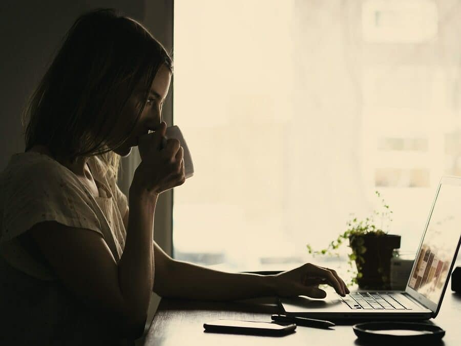 lady drinking from a mug whilst using laptop