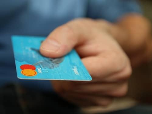 Man Handing Over a Blue Bank Card