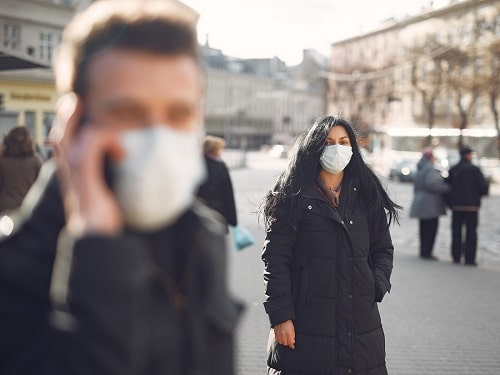 Two People Stood on the Street Wearing Masks